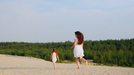 Mom-Plays-With-Her-Daughter-Run-In-The-Sand-Back-View
