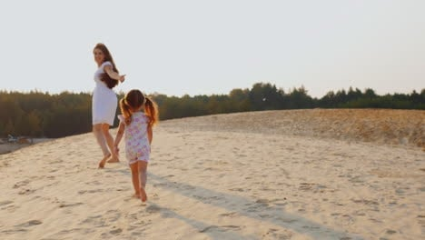 Happy-Young-Mother-Playing-With-Her-Daughter-The-Girl-Runs-After-Her-Mother-On-The-Sand-At-Sunset