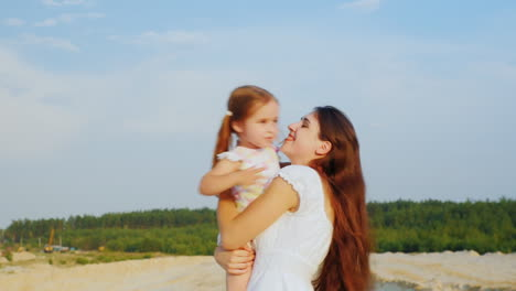 Attractive-Young-Mother-Playing-With-Her-Daughter-Hugging-Sit-In-The-Sand-Against-The-Blue-Sky