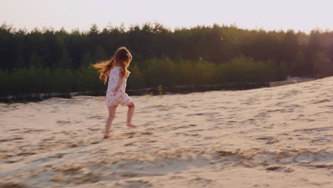 Carefree-Girl-3-Years-Running-Through-The-Sand-Toward-The-Setting-Sun-Against-The-Background-Of-The-