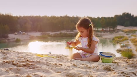 A-Girl-Of-Three-Years-Playing-In-The-Sand-On-A-Background-Of-Lake-And-Recreational