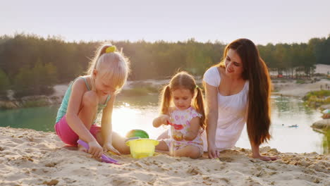 Young-Mother-Plays-In-The-Sand-With-Two-Daughters-At-Sunset-On-The-Background-Of-The-Beautiful-Lake