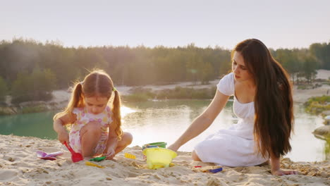 Mom-And-Daughter-Playing-In-The-Sand-Molded-Figurines-From-Sand-Happy-Childhood