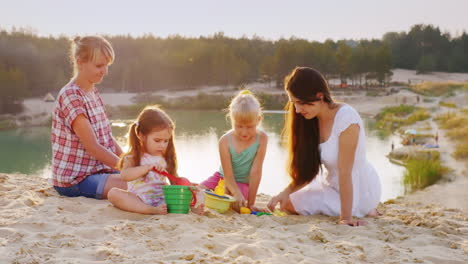 Two-Ladies-Playing-With-The-Kids-In-The-Sand-Against-The-Backdrop-Of-A-Beautiful-Lake-Where-Tourists