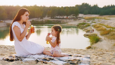 Mother-And-Daughter-Drinking-Juice-From-A-Bottle-With-Tubes-Sit-On-The-Beach-Against-The-Backdrop-Of