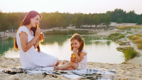 Mum-With-A-Daughter-Three-Years-Relaxing-On-The-Beach-By-The-Lake-Drink-Juice-From-Bottles-With-Tube
