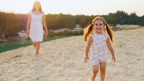 Happy-Childhood-Mother-Playing-With-Her-Daughter-On-The-Beach-Girl-Laughs-And-Runs-Away-From-His-Mot