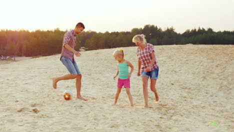 Families-With-A-Child-Playing-Football-In-The-Sand-On-The-Beach