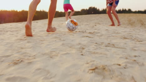 Family-Playing-Football-In-The-Frame-Of-The-Man-Legs-Hit-The-Ball-The-Ball-On-The-Sand