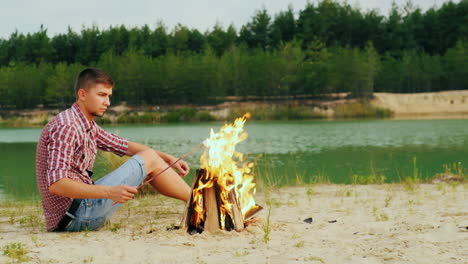 Young-Attractive-Man-Sitting-By-The-Campfire-Roast-Marshmallows-On-A-Stick-Against-The-Background-Of