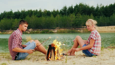 Friends-Of-A-Man-And-A-Woman-Are-Sitting-Around-The-Campfire-Roast-Marshmallows-On-Sticks-Against-Th