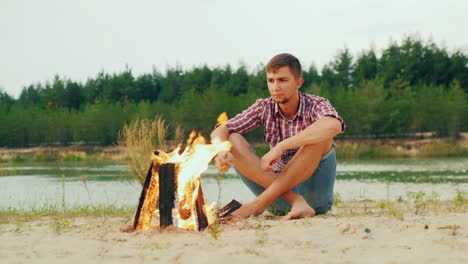 Lone-Serious-Man-Sitting-By-The-Campfire-Roast-Marshmallows-On-A-Stick-Prors-Hq-422-10-Bit-Slow-Moti