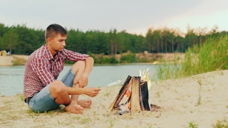 Young-Attractive-Man-Sitting-By-The-Fire-Alone-Fries-Marshmallow-On-A-Stick-Against-The-Background-O