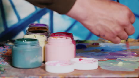 Hand-Painter-Artist-Mixes-Paint-Nearby-Stands-A-Jar-Of-Paint