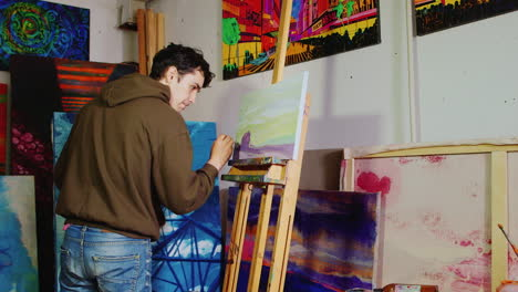 Young-Handsome-Painter-Working-In-The-Studio-Draws-A-Typical-American-Rural-Landscape