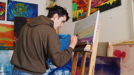 The-Young-Artist-With-A-Smile-On-His-Face-Paints-A-Picture-In-The-Studio