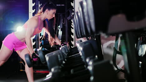 Athletic-Woman-Starts-Training-Trains-Back-Muscles-With-Dumbbells-In-The-Spotlight-Slow-Motion-Prore