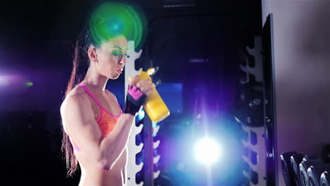 Athletic-Woman-Drinking-A-Protein-Shake-In-A-Shaker-In-The-Gym-In-The-Rays-Of-Spotlights-Sports-Nutr