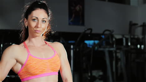 Portrait-Of-A-Female-Athlete-He-Looks-Into-The-Camera-Standing-In-The-Gym