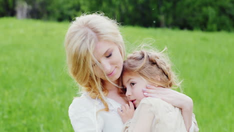 Young-Blonde-Mother-Hugging-Her-Little-Daughter-On-A-Green-Lawn