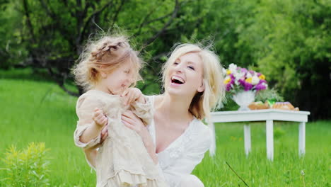 Cute-Little-Girl-In-A-Stylish-Light-Dress-Plays-Fun-With-Her-Mom-In-The-Courtyard-Of-The-House