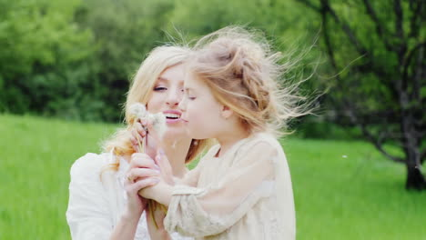 Cool-Blonde-Girl-Blows-A-Dandelion-With-Her-Mother-In-A-Green-Forest