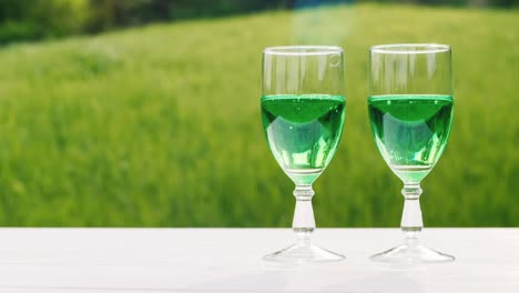 Two-Glasses-With-Green-Lemonade-On-A-Background-Of-A-Green-Lawn-In-A-Spring-Garden