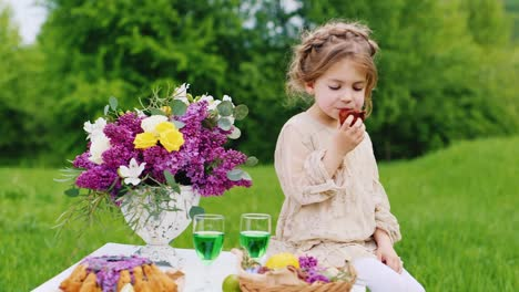 Funny-Blonde-Girl-Sits-On-A-Table-In-The-Garden-And-Eats-Her-Hands-A-Delicious-Cake