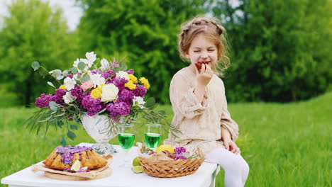 Cute-Little-Girl-In-A-Bright-Smart-Dress-Sits-On-A-Table-And-Eats-Hands-With-Chocolate-Sweets