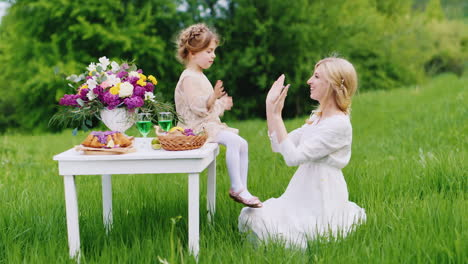 A-Little-Girl-In-A-Smart-Dress-Sits-On-A-Table-And-Plays-Cheerfully-With-Her-Mother-In-The-Hands