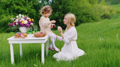 Funny-Girl-With-Blond-Hair-Sits-On-A-Table-In-The-Back-Yard-Of-A-Private-House-And-Mom-s-Feed-Moms-W