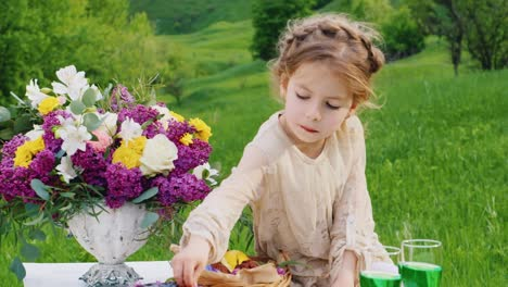 A-Little-Girl-In-A-Smart-Dress-Sits-On-A-Table-Decorated-With-Flowers-And-Eats-A-Chocolate-Finge