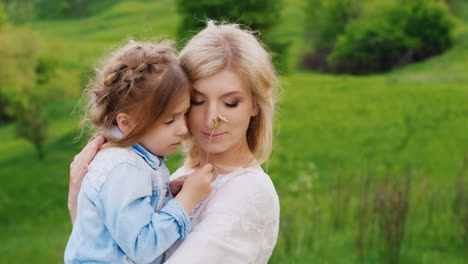 Portrait-Of-A-Pensive-Young-Woman-Who-Holds-Her-Arms-And-Gently-Embraces-Her-Little-Daughter