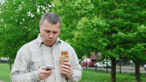 Brutal-Middle-Aged-Man-Walks-Down-The-Street-There-Is-A-Fast-Food-Uses-Your-Smartphone