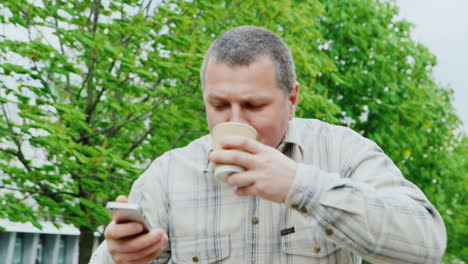 Middle-Aged-Man-In-A-Hurry-Going-Through-The-Park-Drinking-On-The-Go-Coffey-From-The-Cup-And-Looks-A