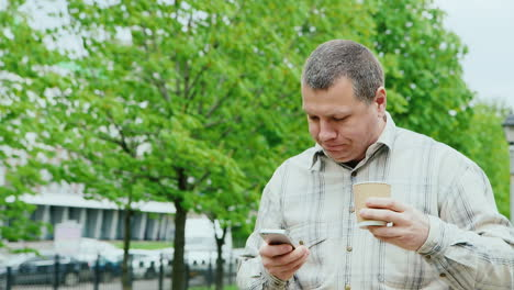 Brutal-Man-Walking-In-The-Park-Using-A-Mobile-Phone-And-Drinking-Coffee-From-A-Paper-Cup