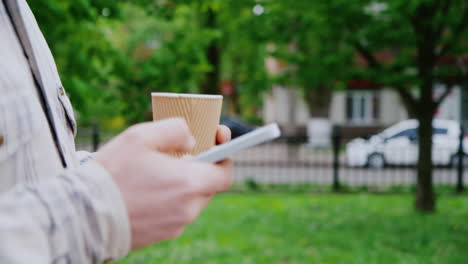 A-Man-Walks-With-The-Phone-And-Coffee-Cup-In-The-Frame-Only-Hands-Seen