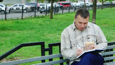 Man-Eating-Fast-Food-On-A-Park-Bench-Writes-Something-In-A-Notebook