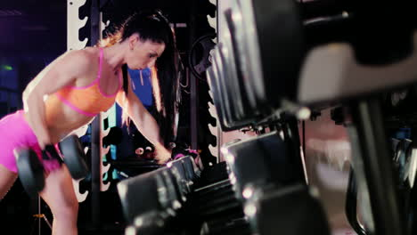 Female-Athlete-Doing-Exercise-With-A-Dumbbell-In-The-Gym-In-The-Spotlight