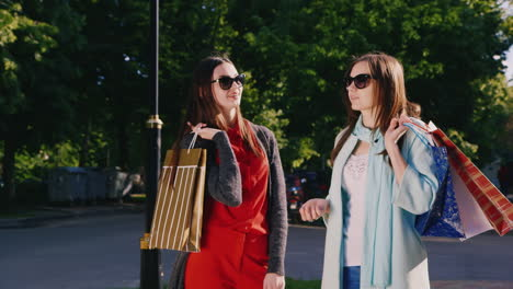 Steadicam-Shot-Two-Young-Women-With-Shopping-Bags-Talking-In-The-Street-Smiling