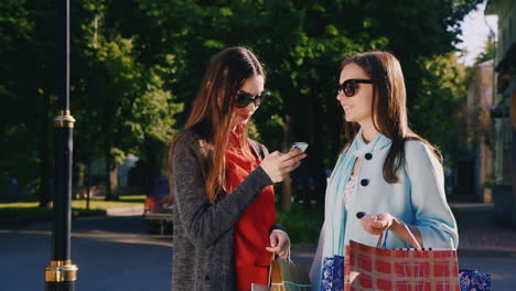 Two-Girl-Friends-With-Shopping-Bags-Used-Smartphone-Outdoor-Hd-Video