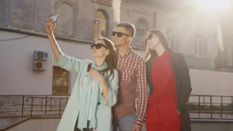 Friends-Two-Women-And-A-Man-Doing-Selfie-In-The-Sun-Against-The-Background-Of-An-Old-Building-Hd-Vid
