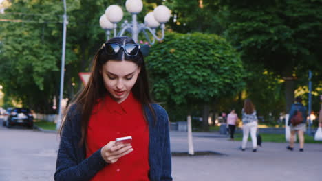 Attractive-Woman-Walking-Down-The-Street-Enjoying-The-Smartphone-Is-Typing-Looks-Posts