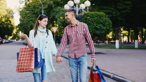 Young-Couple-Walking-Through-The-City-With-Shopping-Bags-They-Are-Happy-Smiling-Talking