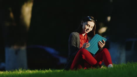 Young-Woman-Enjoys-The-Tablet-In-The-Park-Sitting-On-The-Grass-His-Face-Lit-By-The-Evening-Sun-Hd-Vi