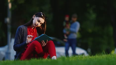 Stylish-Woman-Sitting-On-The-Grass-In-The-Park-Enjoying-The-Tablet-In-The-Background-People-Walk-Hd-