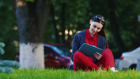 Stylish-Woman-Sitting-On-The-Grass-In-The-Park-Enjoying-The-Tablet-In-The-Background-People-Walk