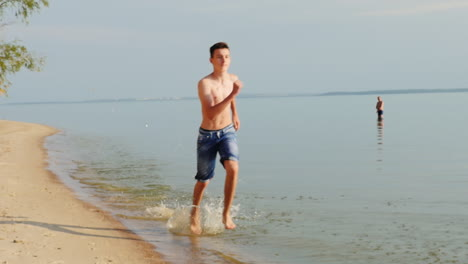 Teen-15-Years-Running-On-The-Beach-On-The-Water-Slow-Motion
