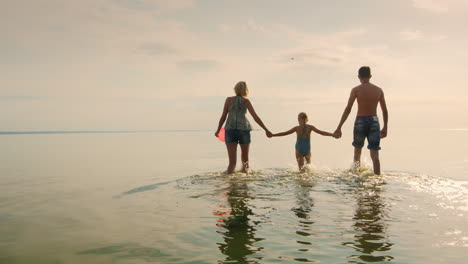 Mother-And-Childrens-Walking-On-The-Shallow-Water-At-Sunset