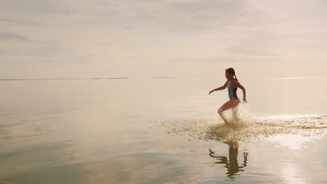 Carefree-Girl-Of-7-Years-Running-On-The-Water-From-Her-Feet-Flying-A-Lot-Of-Splashing-Slow-Motion